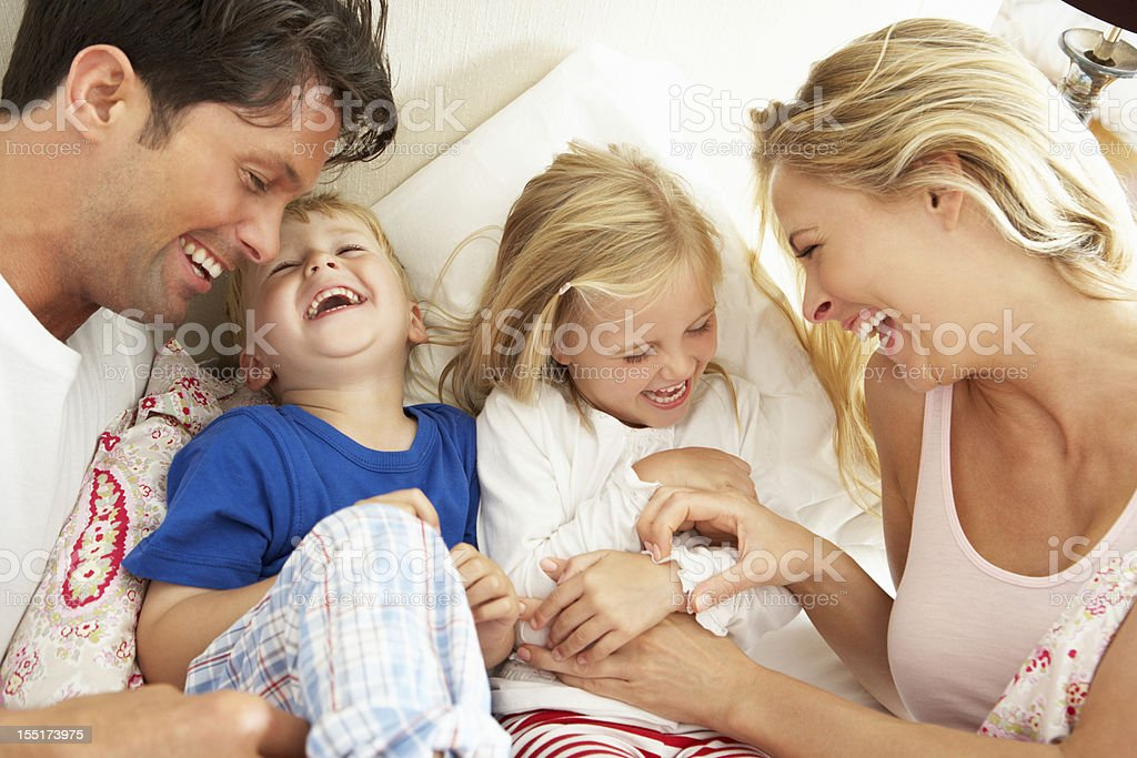 Family Relaxing Together In Bed stock photo