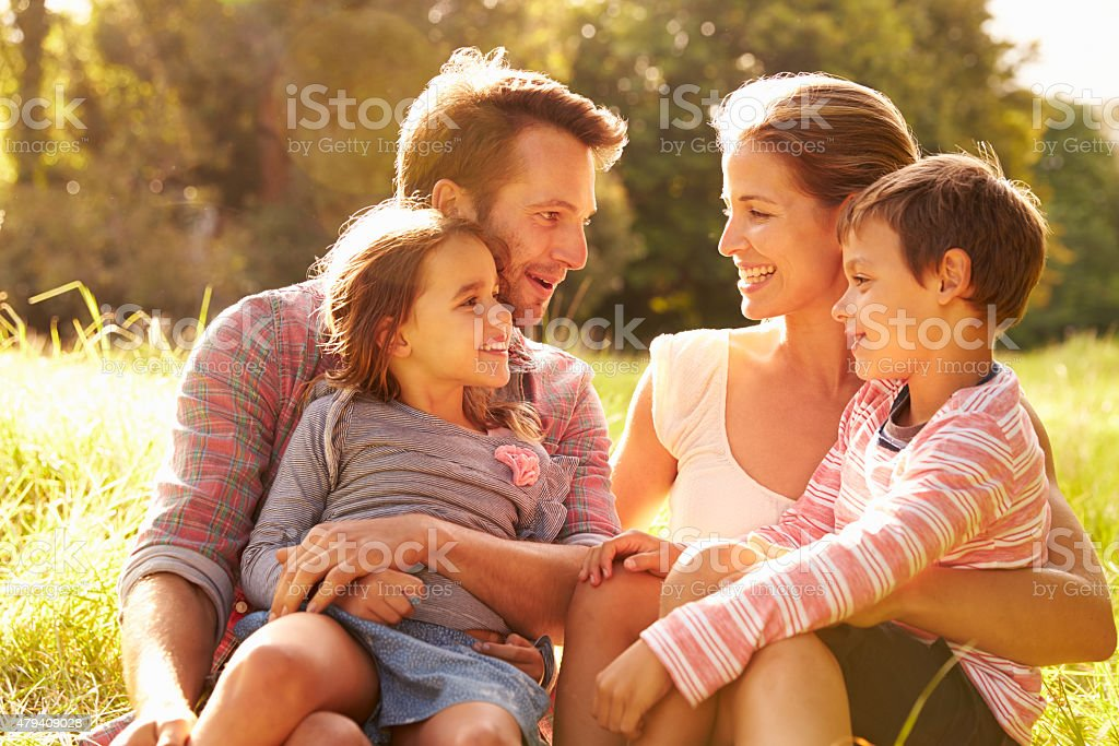 Family relaxing together outdoors, looking at each other stock photo