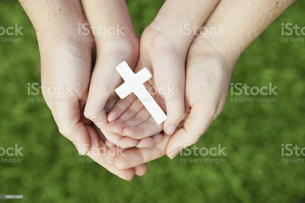 A child and mother\'s cupped hands holding a small white cross.
