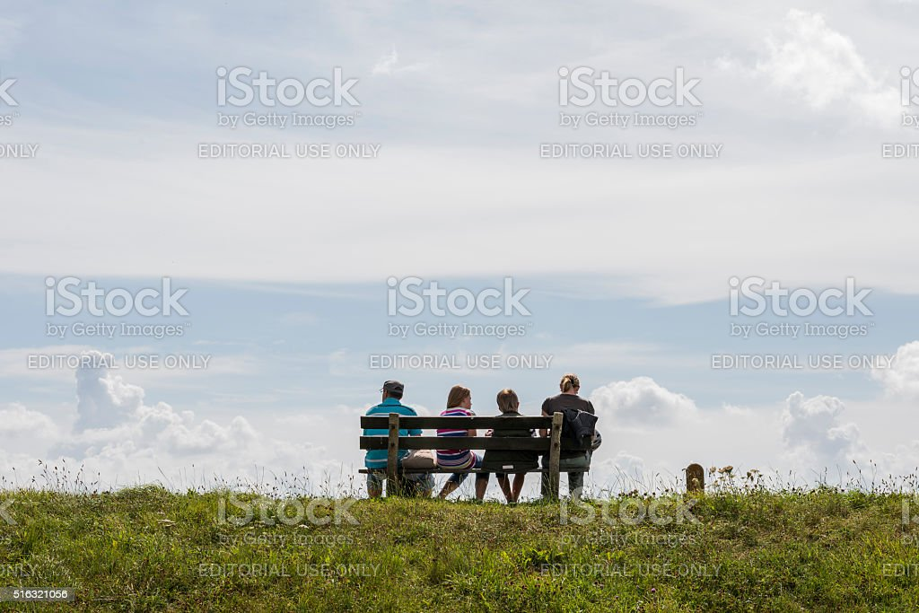 Family resting on dike stock photo