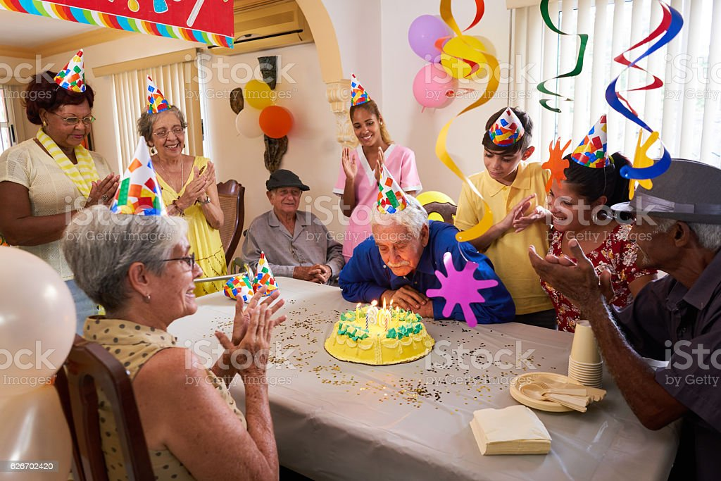 Family Reunion For Birthday Party Celebration In Retirement Home stock photo