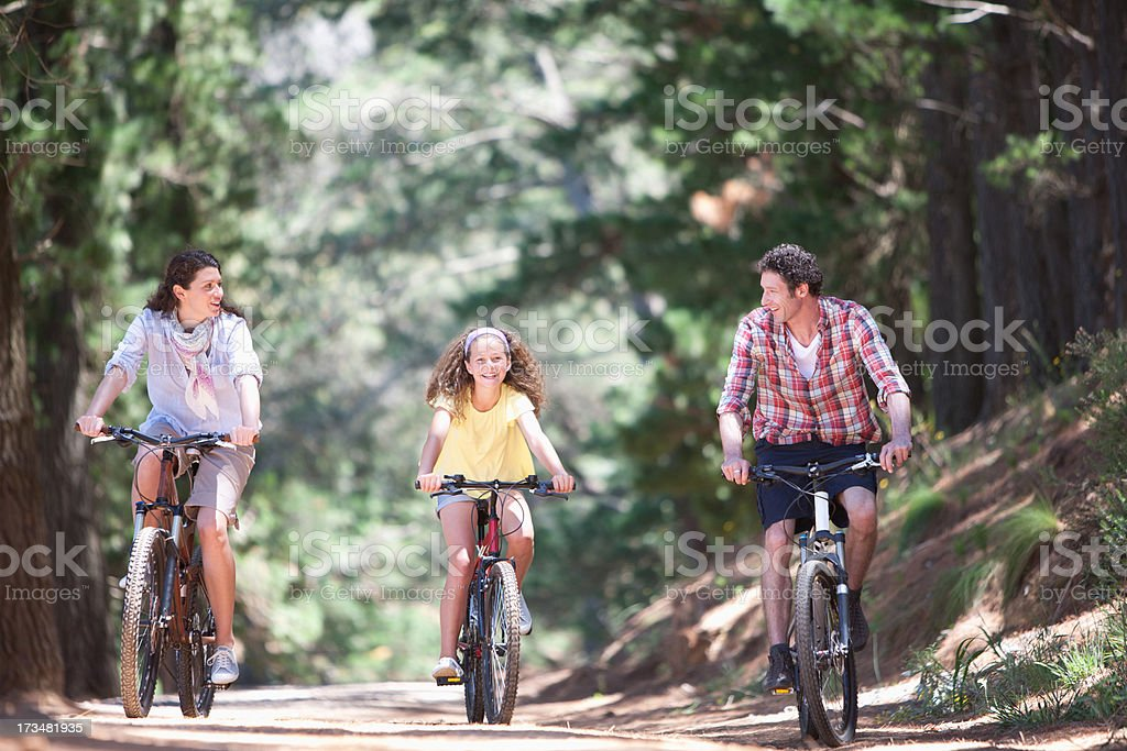 Family riding bicycles in woods royalty-free stock photo