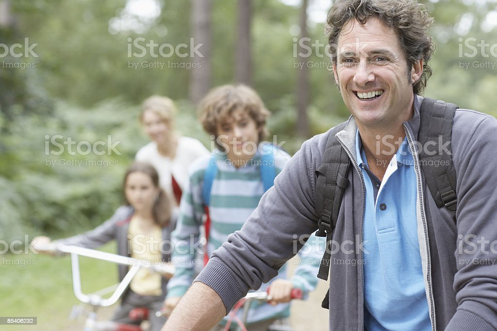 Family riding bikes outdoors stock photo