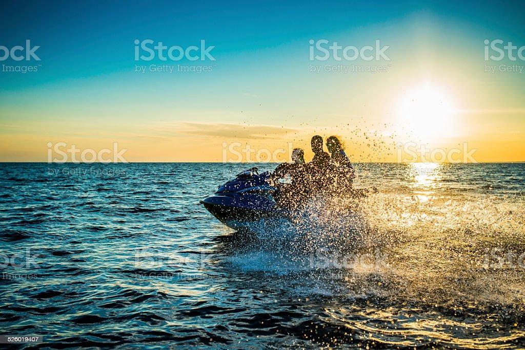 Family Riding  Jet Boat at Sunset stock photo