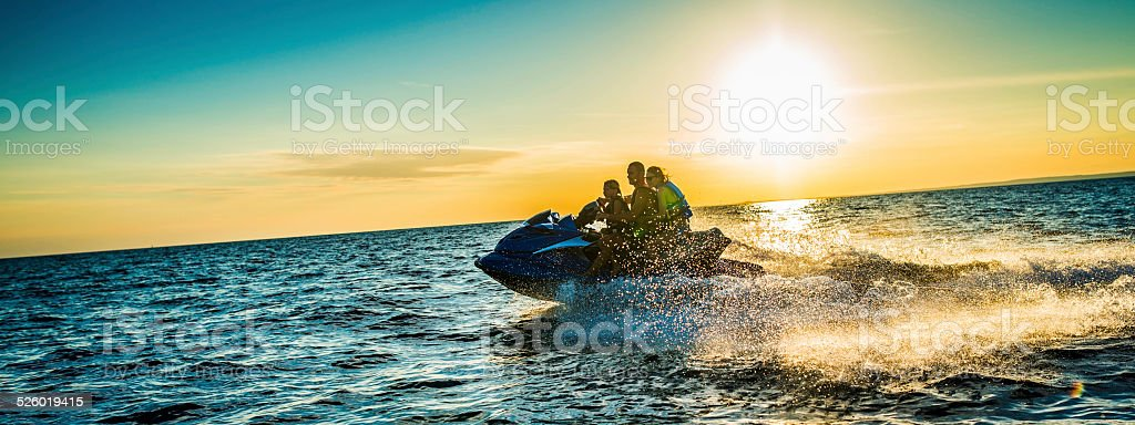 Family Riding  Jet Boat at Sunset stock photo