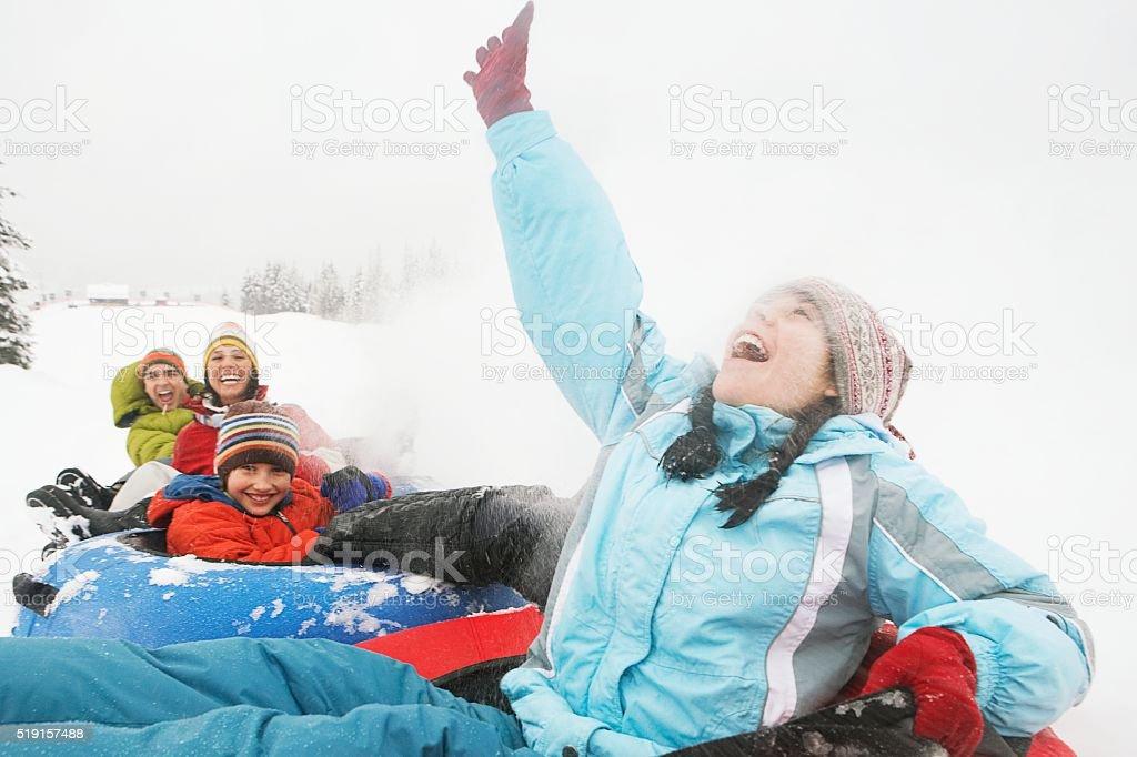 Family riding snow tubes stock photo