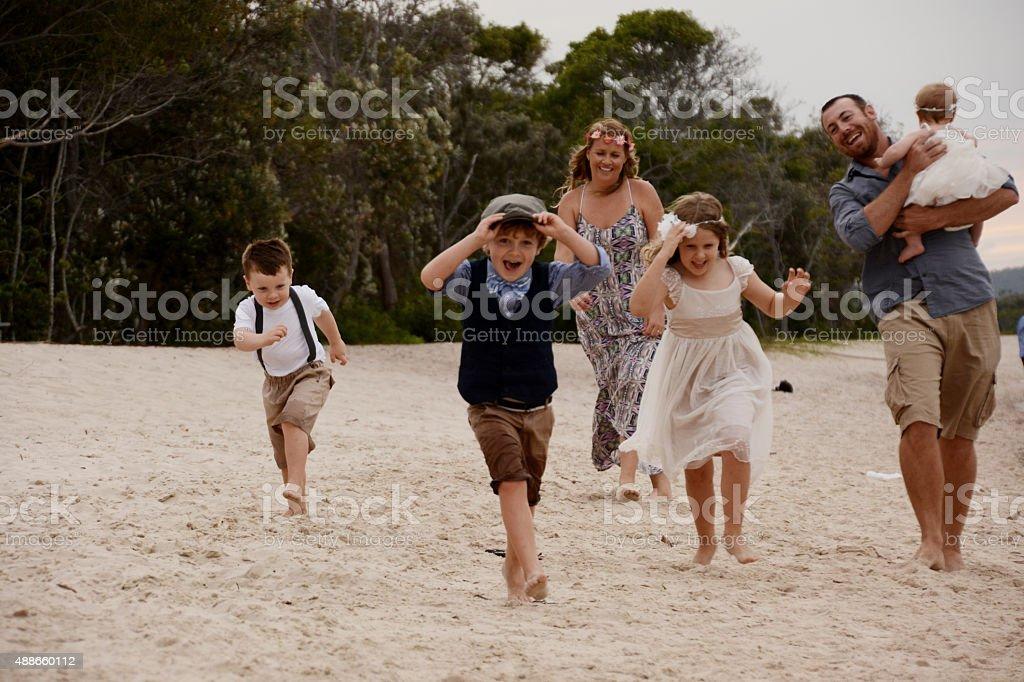 Family running along beach stock photo