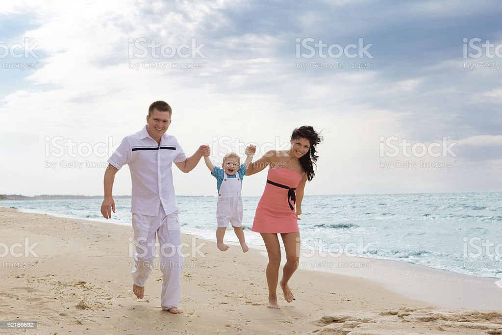 Family running along the beach royalty-free stock photo