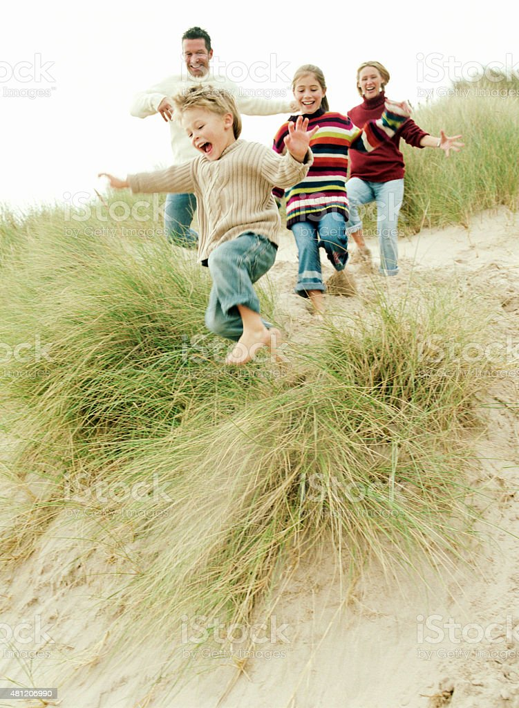 Family running down a grassy hill stock photo