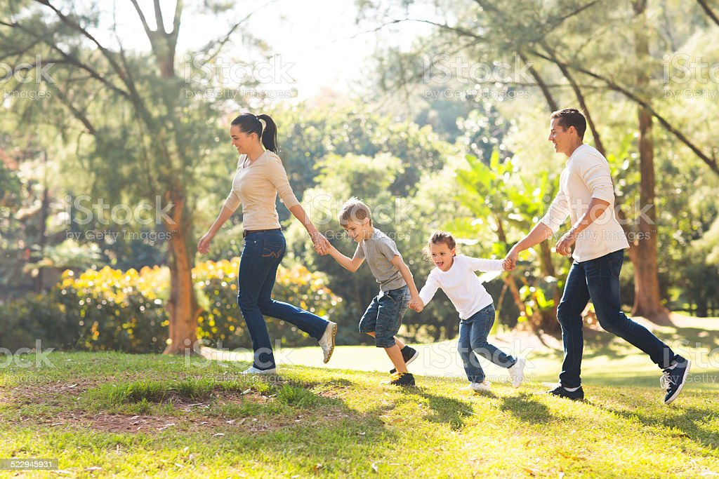 family running in forest stock photo