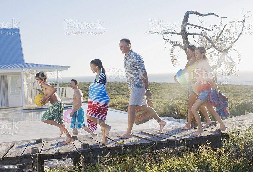 Family running on pier near swimming pool royalty-free stock photo