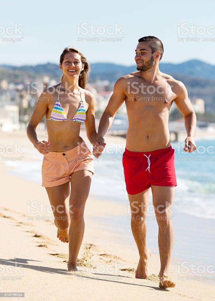 family running on the shore stock photo