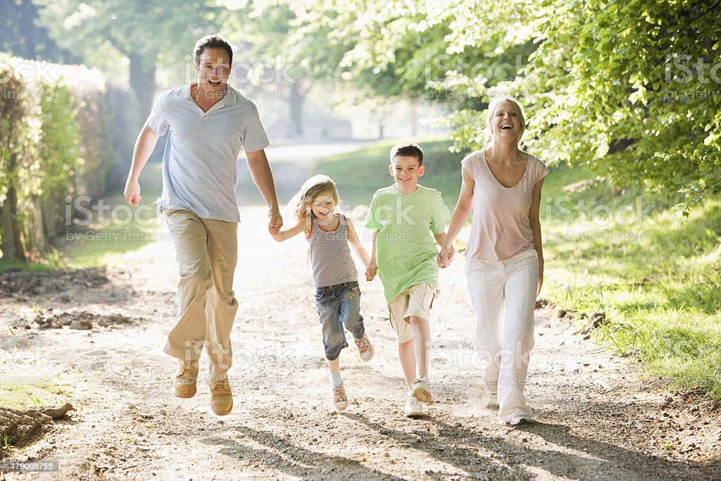 Family running outdoors holding hands and smiling stock photo