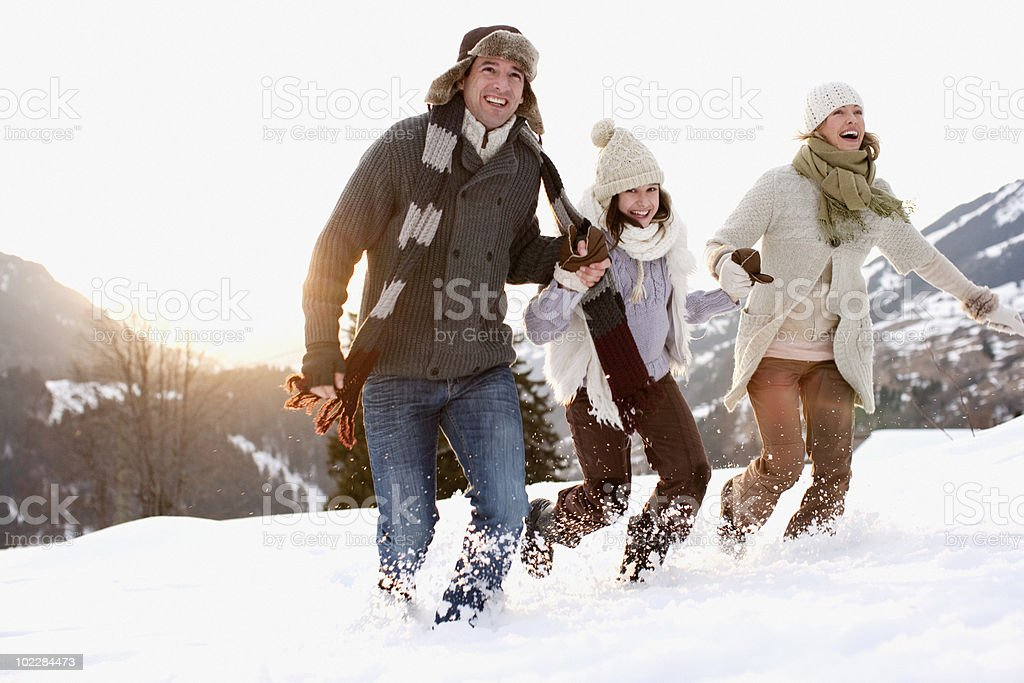 Family running outdoors in snow stock photo