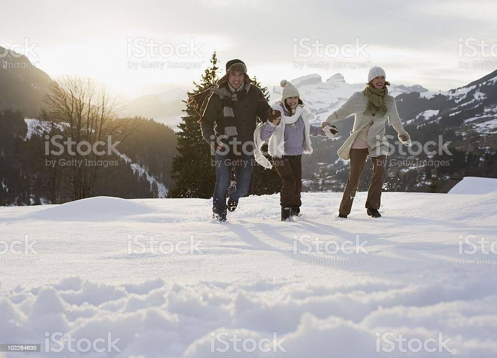 Family running outdoors in snow royalty-free stock photo