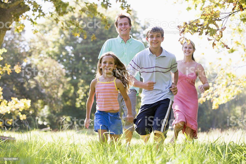 Family running outdoors smiling royalty-free stock photo