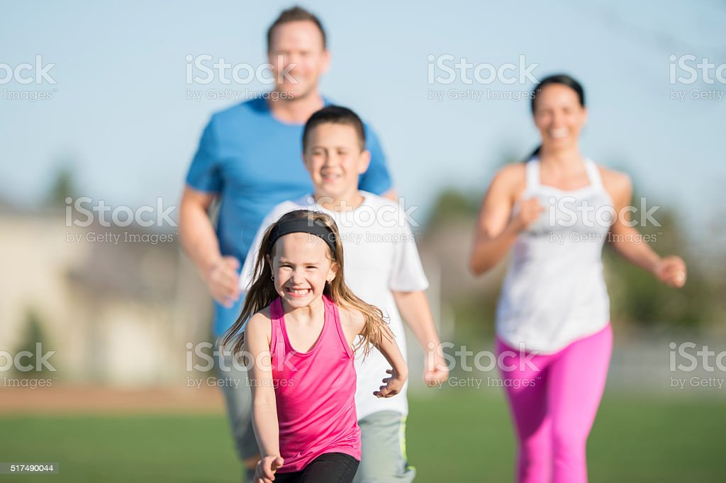 Family Running Together in the Park stock photo