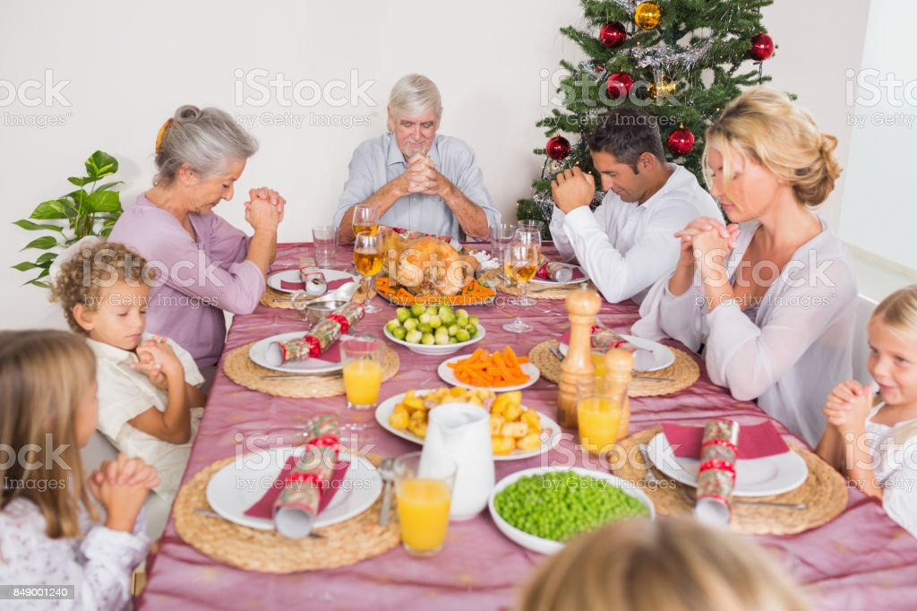 Family saying grace before christmas dinner stock photo