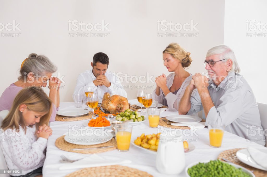 Family saying grace before eating a turkey stock photo