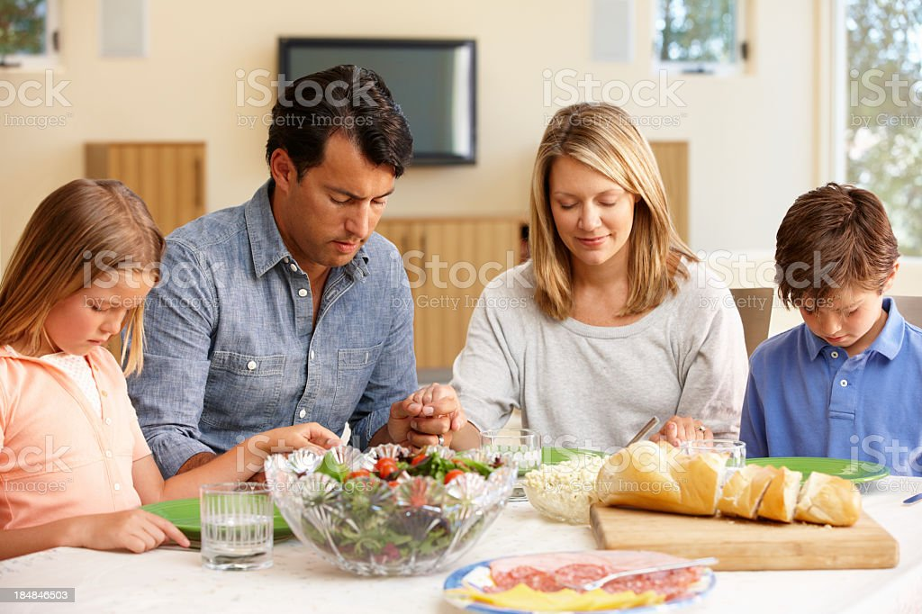 Family saying grace before meal stock photo