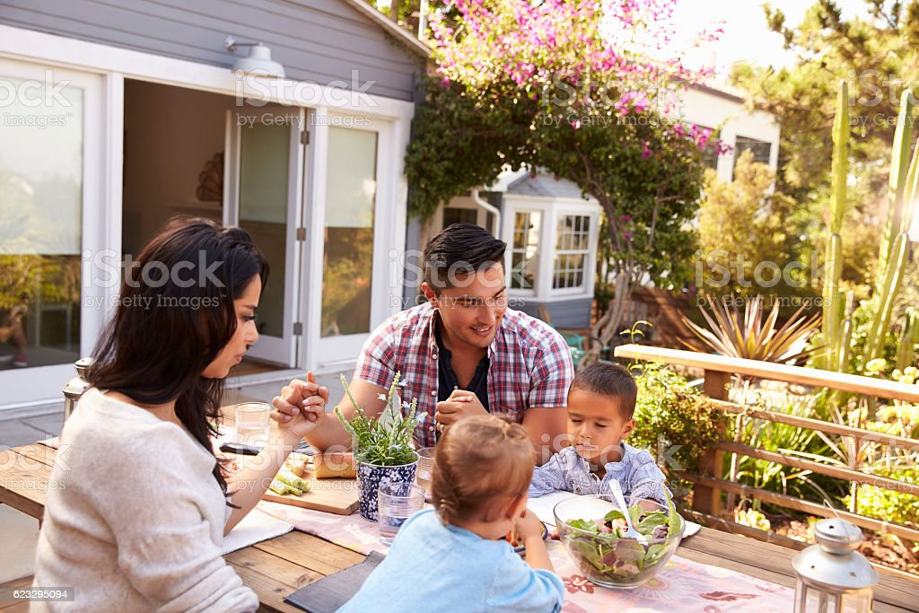 Family Saying Grace Before Outdoor Meal In Garden stock photo