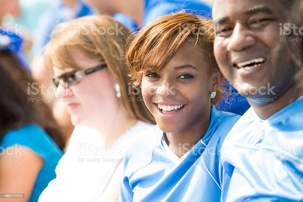 Family seated in stadium stands cheering for favorite sports team royalty-free stock photo