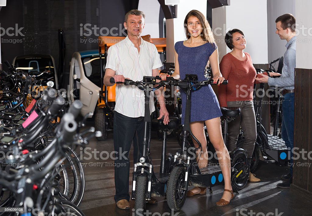 Family selecting electric bikes at rental stock photo