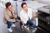 Family selecting modern dishwasher