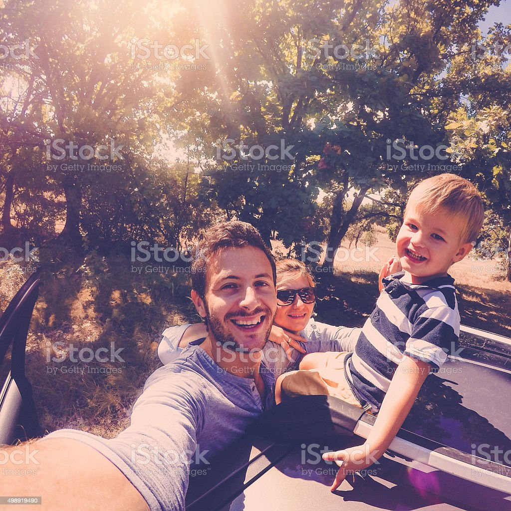 Photo of cute little family posing for the selfie in the nature,...
