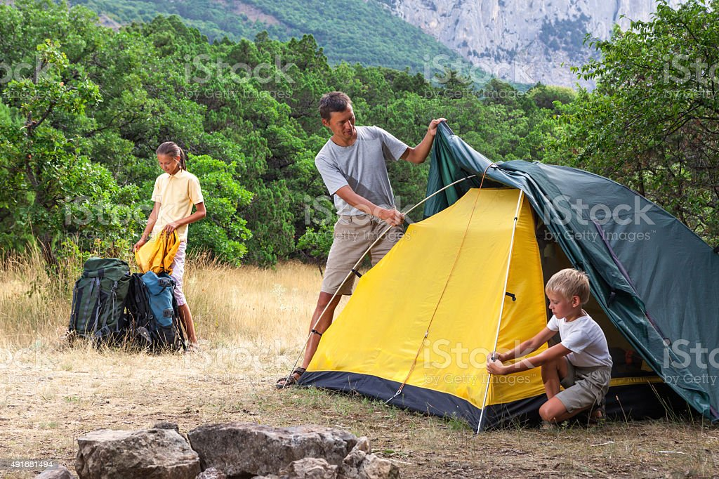 Family setting a tent in the meadow stock photo