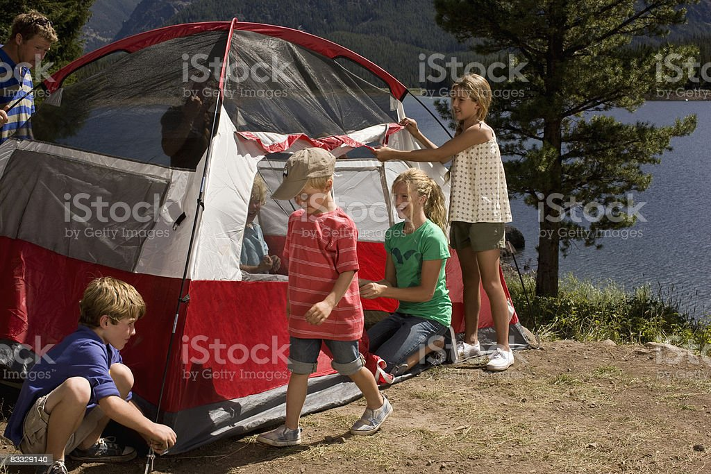 Family setting up tent by lake stock photo