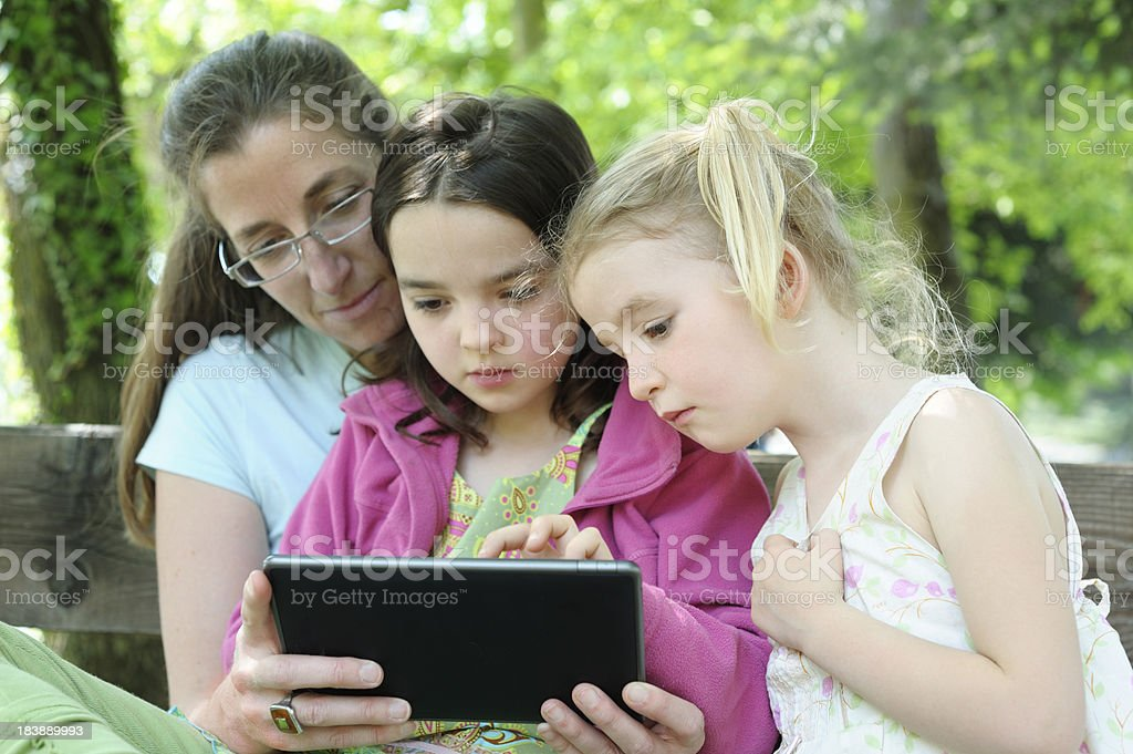 family sharing an e-story in the park stock photo