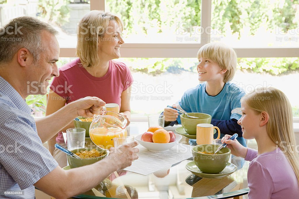 Family sharing breakfast together in morning at home stock photo
