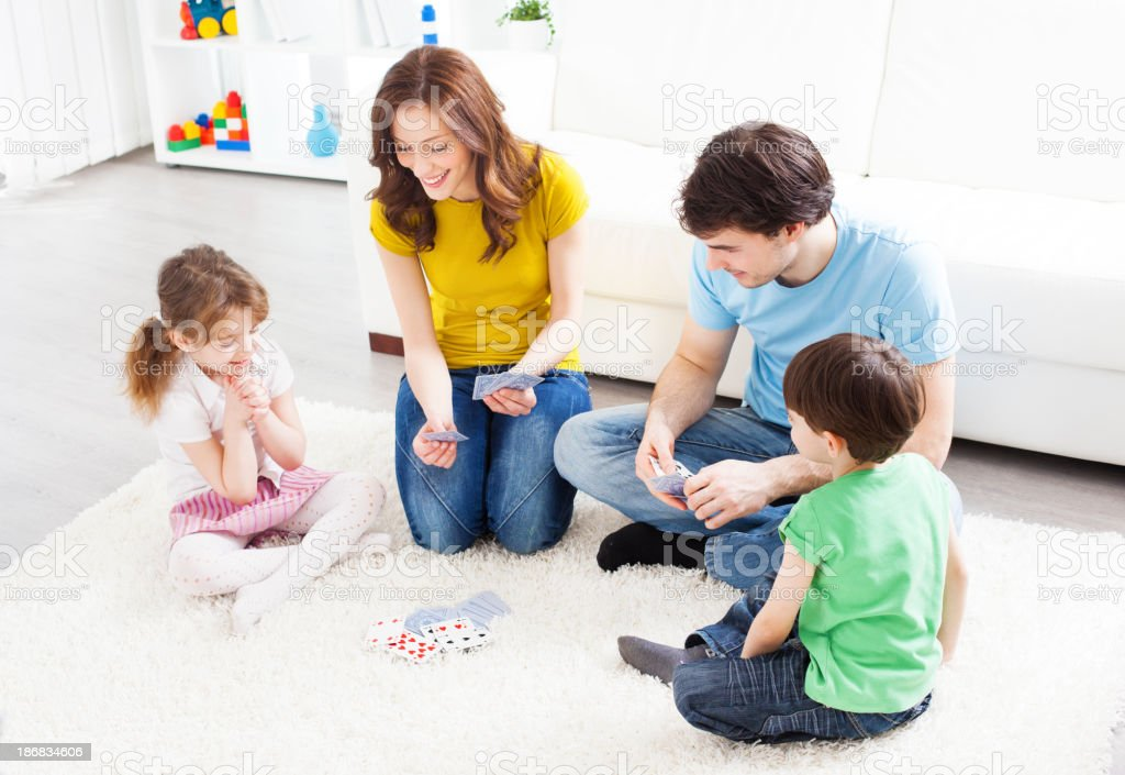 Family sitting and playing cards in living room stock photo