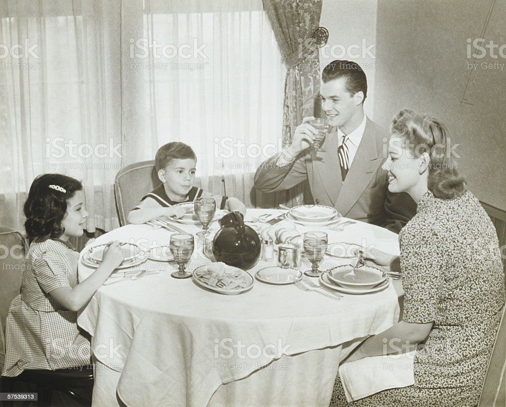 Family sitting around table, having meal, children (4-5) (6-7), (B&W) stock photo