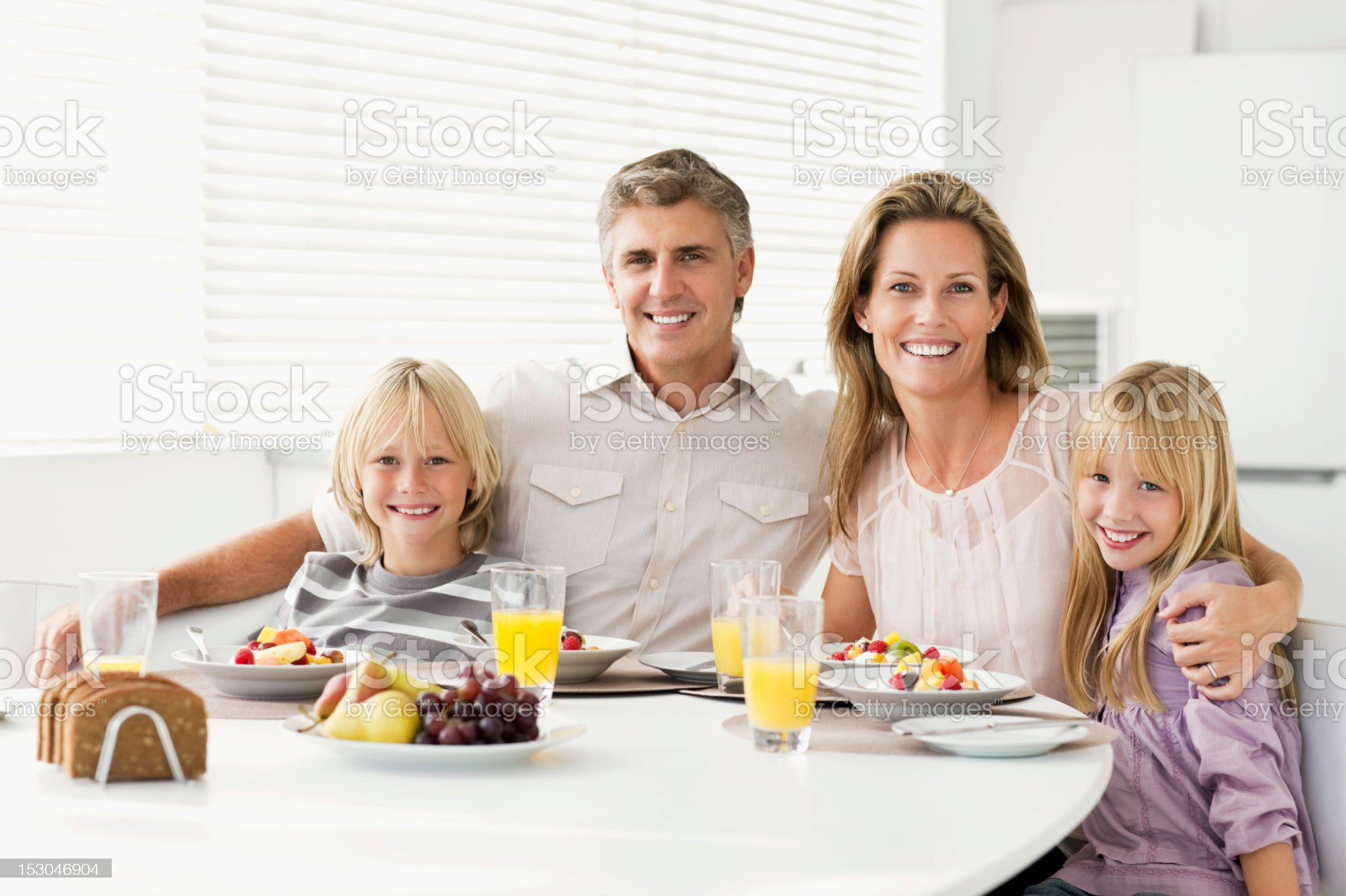 Family Sitting at Breakfast Table Smiling royalty-free stock photo