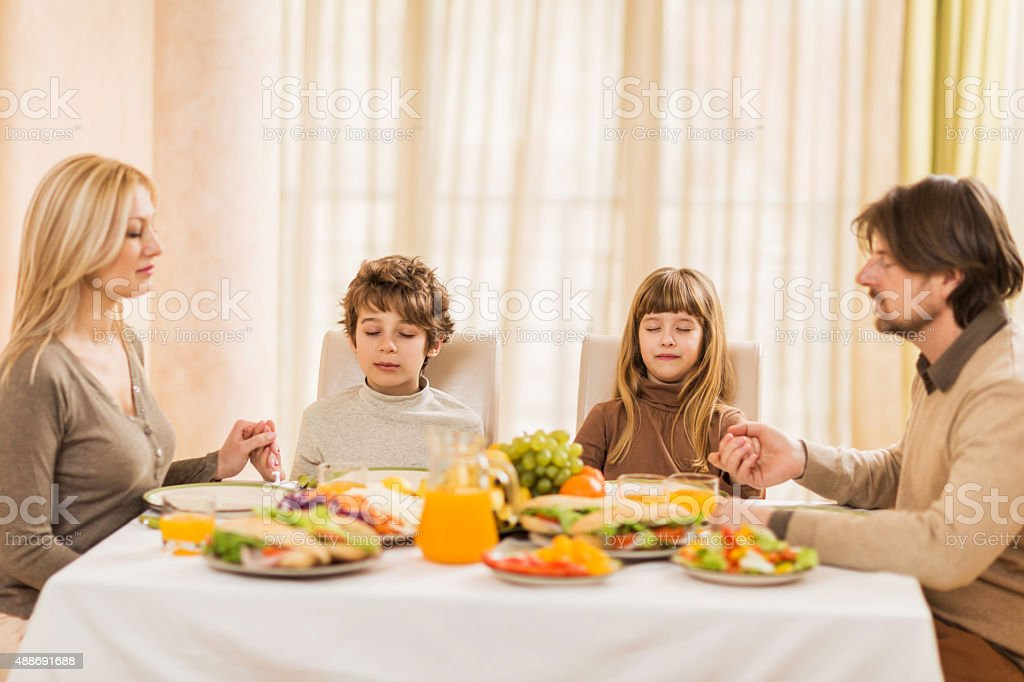 Family sitting at dinning table and praying before meal. stock photo