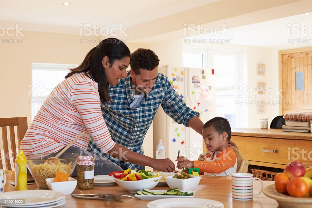 Family Sitting At Table In Kitchen Eating Meal With Son stock photo