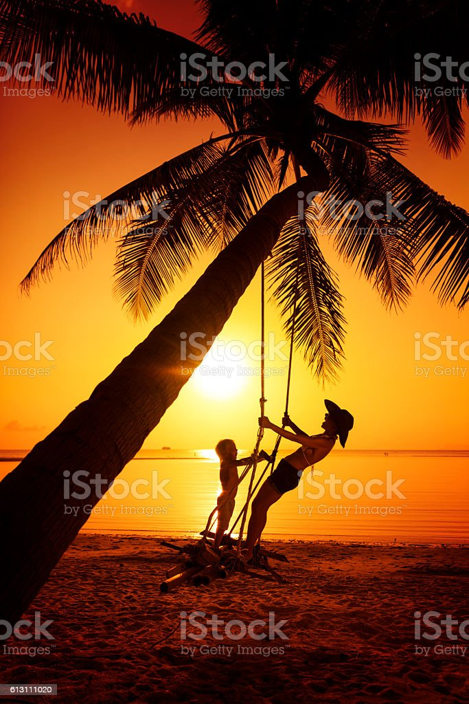 Family sitting at tropical swing stock photo