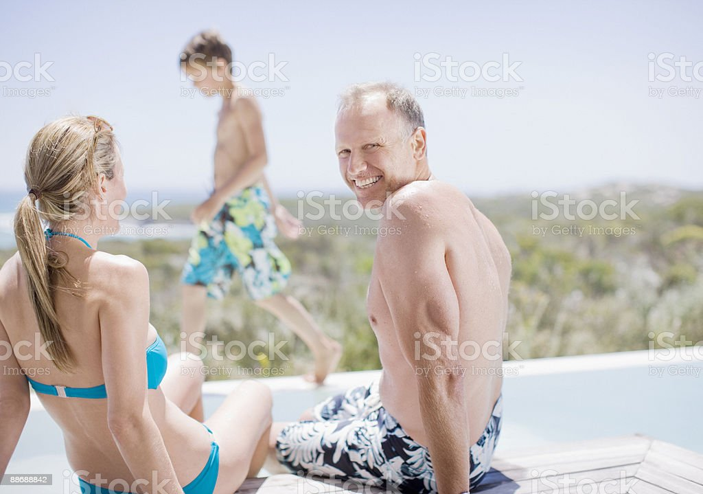 Family sitting by swimming pool royalty-free stock photo