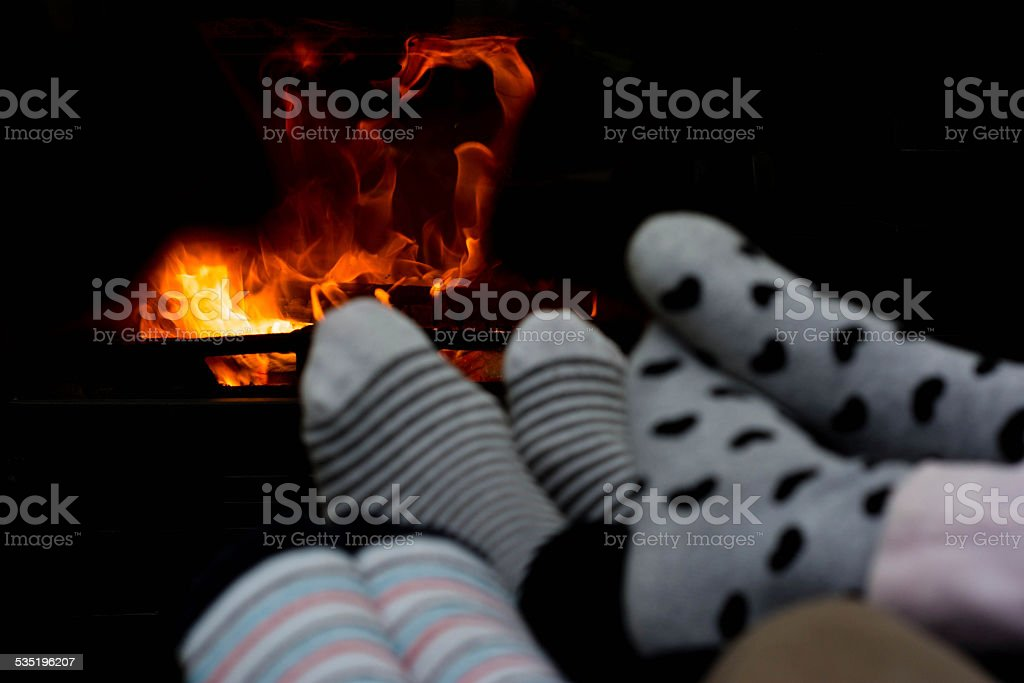Family sitting by the fireplace stock photo