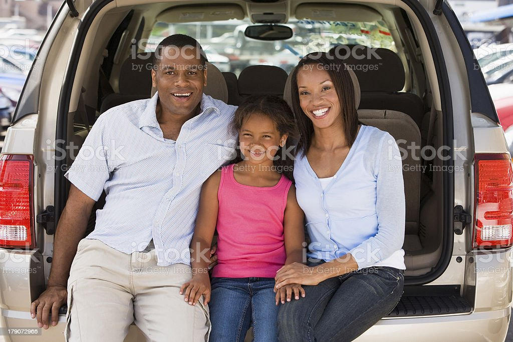 Family sitting in back of van smiling royalty-free stock photo