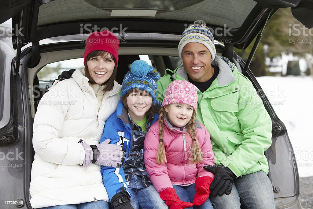 Family Sitting In Boot Of Car Wearing Winter Clothes stock photo