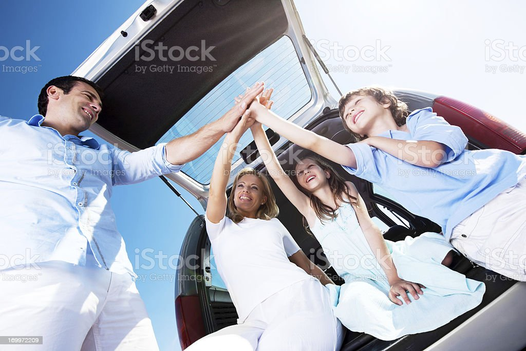 Family sitting in car trunk and giving high five. royalty-free stock photo