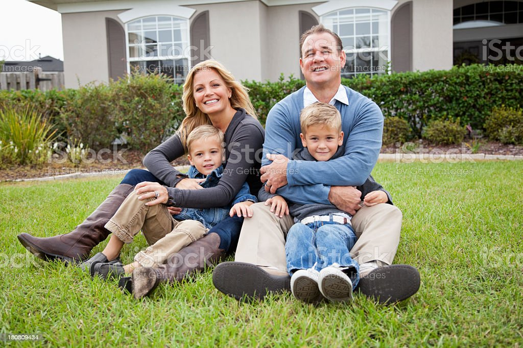 Family sitting in front of house stock photo