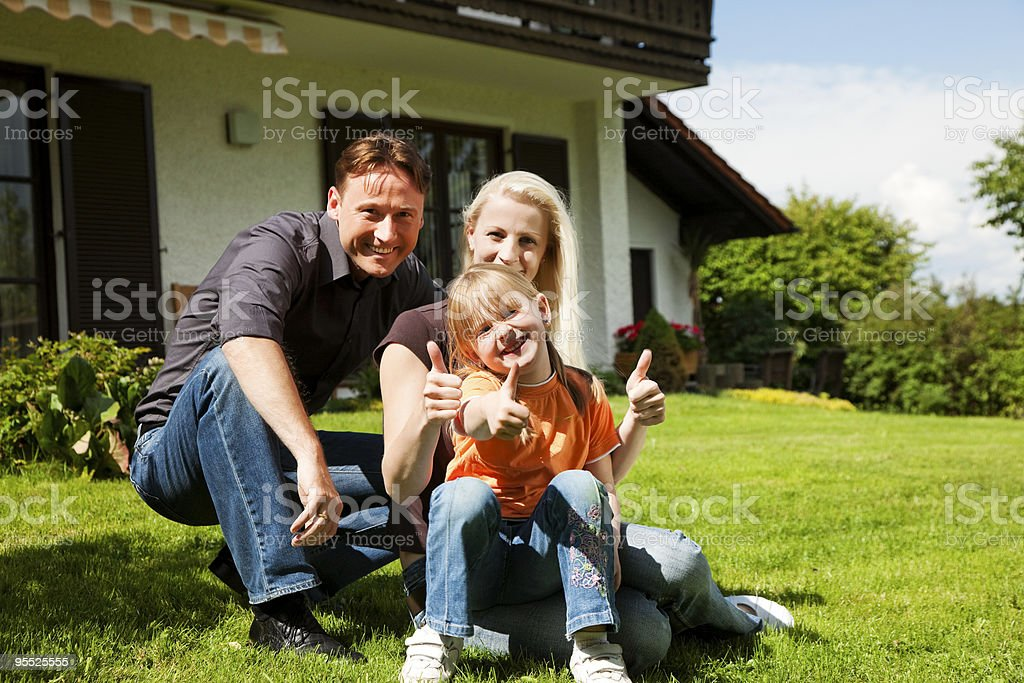 Family sitting in front of their home royalty-free stock photo