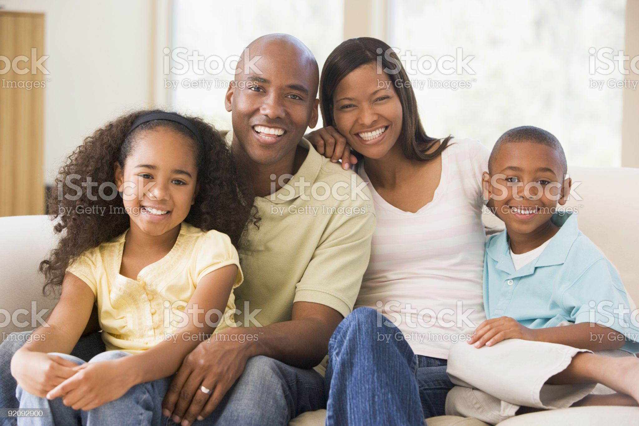 Family sitting in living room smiling royalty-free stock photo