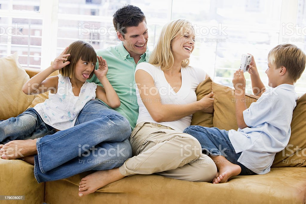 Family sitting in living room with digital camera smiling royalty-free stock photo