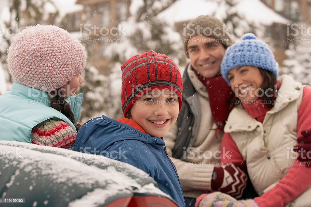 Family sitting in sleigh in snow stock photo