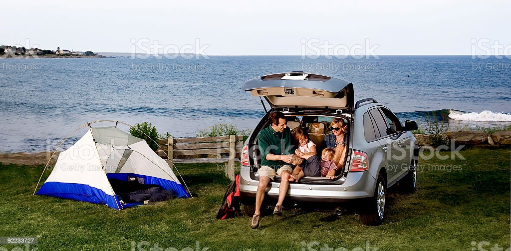 A family sitting in the back of an SUV outdoors stock photo